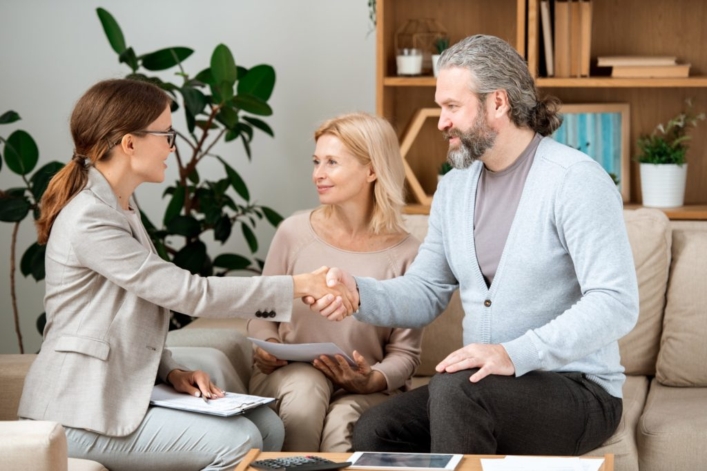 Young real estate agent congratulating mature couple with buying new house